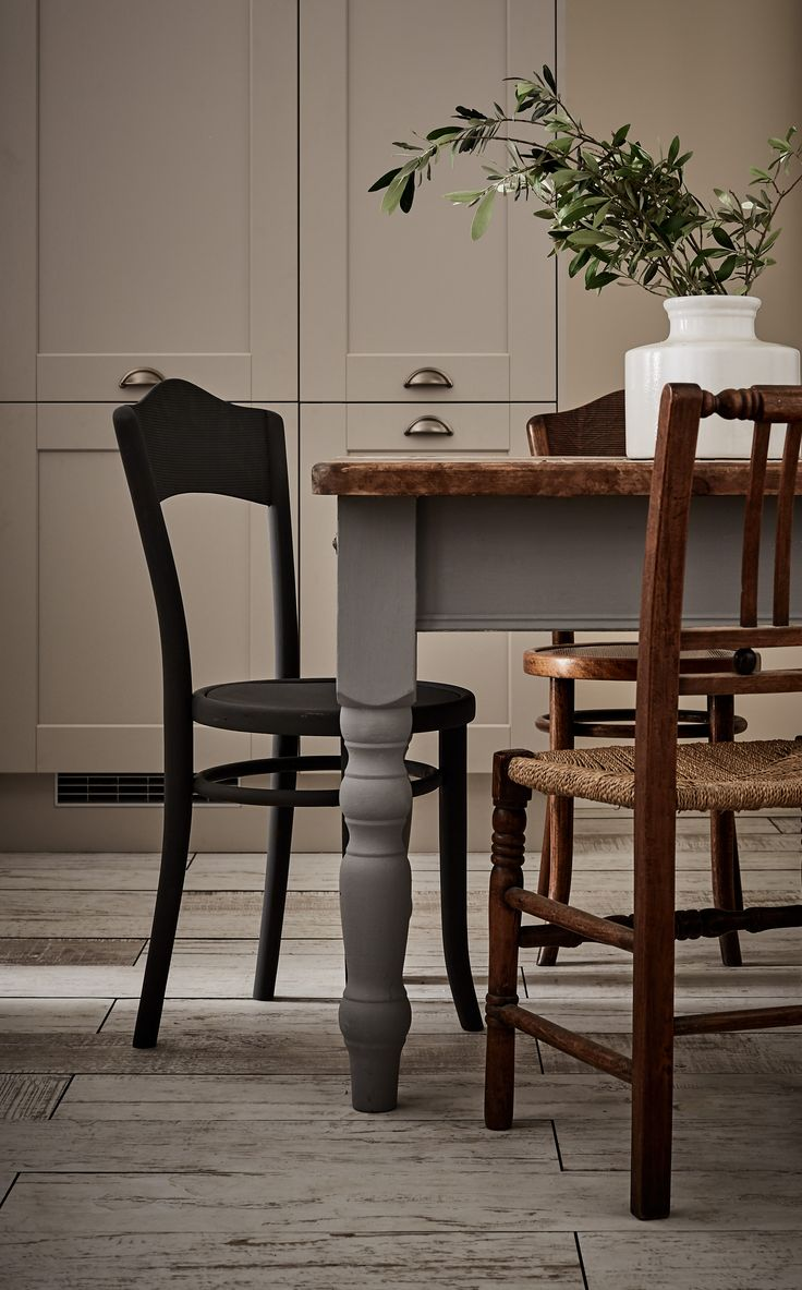 Mix and match reclaimed chairs in similar tones to complete the Shaker look. Take a look at Howdens for Shaker kitchen design ideas.