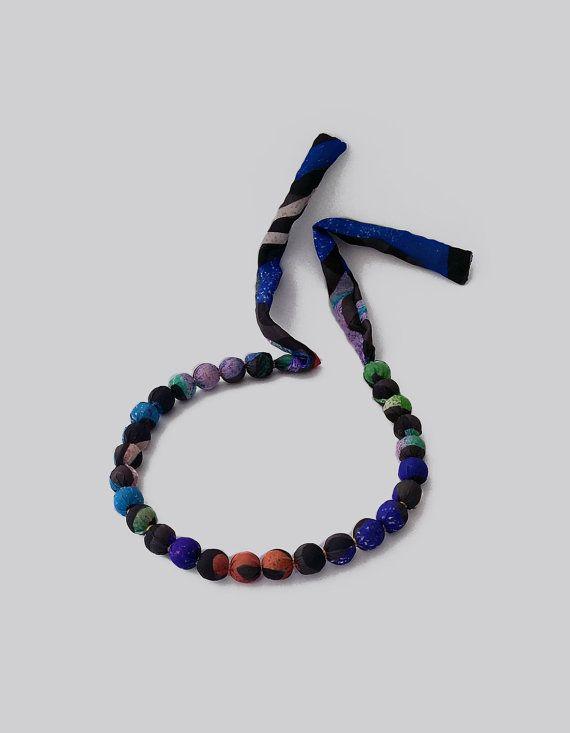 Exclusieve zijde gewikkeld ketting gemaakt van materialen houten kralen, gescheiden door kleine metalen ringen. De sjaal als ketting heeft een elegante combinatie van zwart, wit, groen, blauw en zacht oranje. De verstelbare uiteinden zijn los, zodat je met een boog binden kunt als je van de rust op het gebied van sleutelbeen of met een knoop als u verkiest om het te dragen langere ketting. De ketting maakt een geweldige accessoire voor een avond outfit; het ziet er geweldig uit met een…