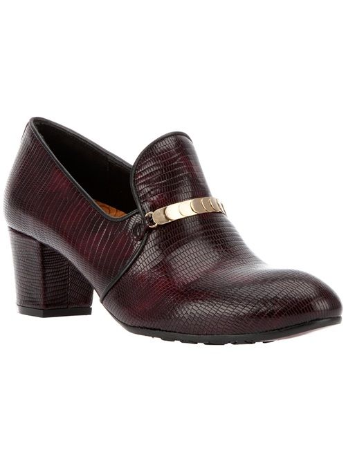 Burgundy court shoe from Chie Mihara featuring an almond toe, a gold-tone layered strip buckle detail, a leather sole, and a tapered block heel.