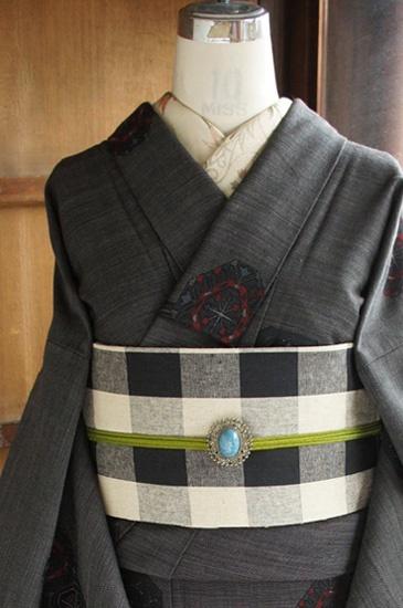 黒とグレーの糸で繊細なチェック模様が織り出された黒に近い沈んだグレーの地に、ステンドグラスやヨーロッパのアンティークの宝石箱を思わせるようなロマンチックな装飾模様がデザインされたウールの単着物です。