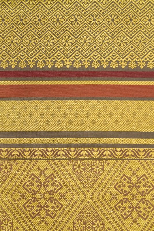 Bali Fabric Traditional Balinese inspired embroidered cotton fabric with small, eclectic design in Orange, Gold and Ochre.  Suitable for Curtains and General Domestic Upholstery.