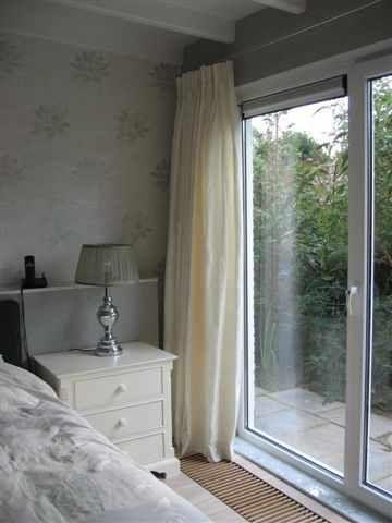 Slaapkamer met gordijnen van ruwe zijde offwhite.