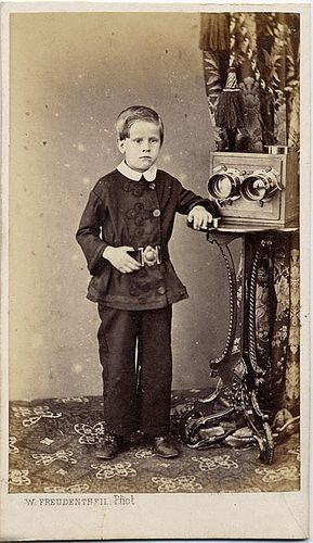 Boy with a Stereo Camera    This European carte-de-visite is by W. Freudentheil. It seems unlikely that the grim faced little boy in the strange coat could manage the large stereo camera beside him.