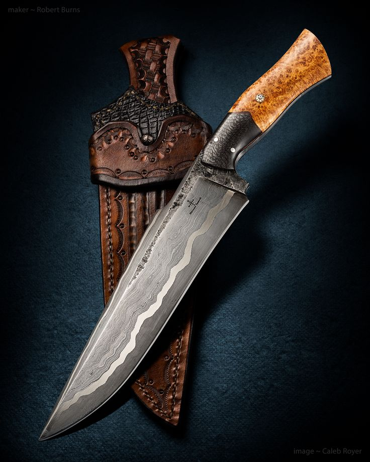 """Maker: Robert Burns Website: wildernessironworks.org Steel: """"Go Mai"""" 300 layer 15n20/1095, with pure nickel over a W2 core. Blade length: 9 1/4"""" Overall Length: 14 3/4"""" Handle: Carbon Fiber & stabilized black ash burl with leather spacer. Pins: Stainless Steel & Mosaic Sole Authorship"""