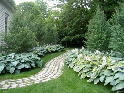 This meandering garden path uses granite cobblestones for a clean yet casually natural look. Design by KaneScapes in Cooperstown, NY.
