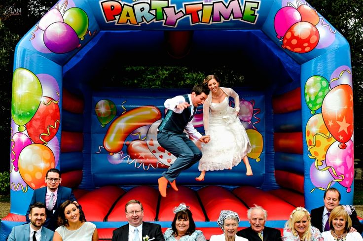 Creative group wedding photographs on a bouncy castle at Orchardleigh House