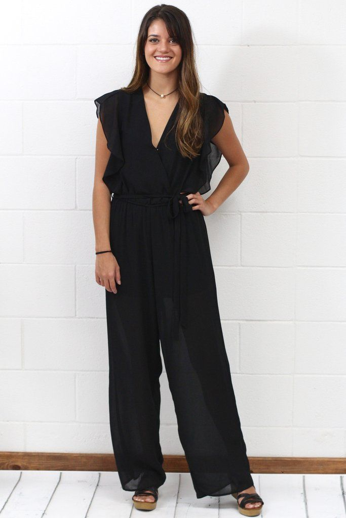 "Short sleeve jumpsuit with ruffled accents and waist tie. Loose fit. Elastic waistband. Lined to mid-thigh...like shorts underneath...with rest of pant being somewhat sheer. Surplice body with closure. Black in color. Model is 5'9"" with a 2.5"" wedge on."