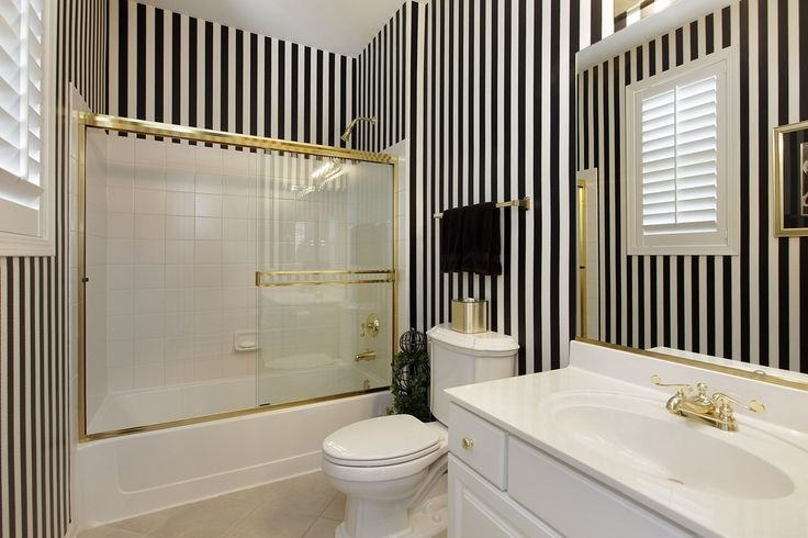 Full Bathroom with Corian counters, limestone tile floors, Flush, Black and White Stripe Norwall Wallpaper (5.45 yards)