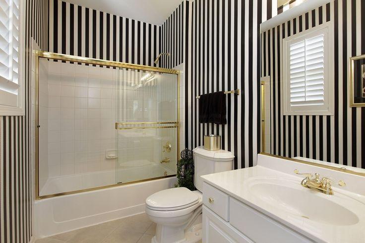 Full Bathroom with Corian counters, limestone tile floors, Flush, Black and White Stripe Norwall Wallpaper (5.45 yards)