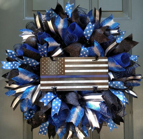 Show your support for Law Enforcement with this Thin Blue Line American Flag Wreath. Constructed on a wire wreath frame with four different patterns of Poly Deco Mesh: Metallic Navy/Royal, Metallic Black, Deluxe Wide Foil Royal Blue and Deluxe Wide Foil Metallic Black. Four different coordinating patters of wire ribbon are layered throughout this handcrafted wreath. Three eye catching ornaments draw your attention to the glossy, aluminum metal American Flag and Thin Blue Line sign. They…