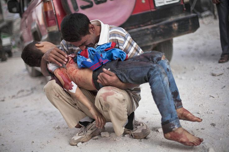 A man mourns the body of his child near the Dar El Shifa hospital in Aleppo, where three suicide bombers blew 3 car bombs, leaving 34 dead.