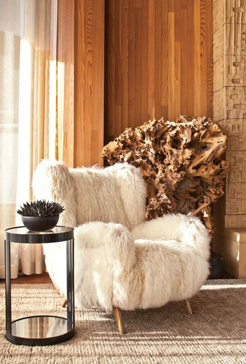 Kelly Wearstler 70's modern beach house living room wood paneling fur covered chair driftwood