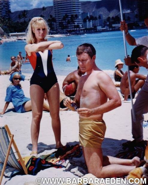 "Barbara and Larry on location in Hawaii while filming ""I Dream of Jeannie."" This shot was taken between shots when Jeannie blinked a fur coat onto Major Nelson out on the beach. Barbara had to stand still and hold the position while wardrobe dressed Larry in the fur coat and reset the scene. -Team Eden"