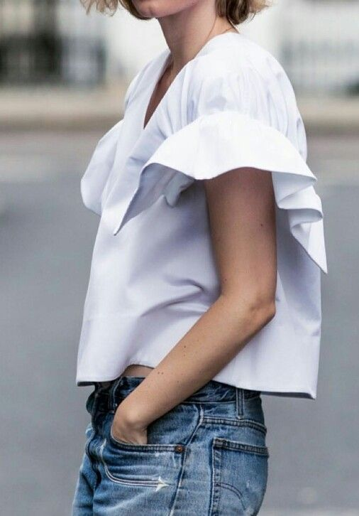 A simple frill can elevate a classic white blouse. Emilia loves frills.