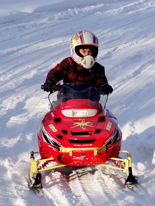 Un enfant faisant de la motoneige à Arctic Circle Snowmobile Park au Village du Père Noël à Rovaniemi