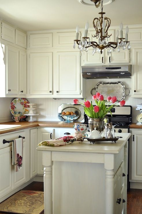 Chic Cottage Kitchen With Cream Cabinets Paired With Wood Countertop