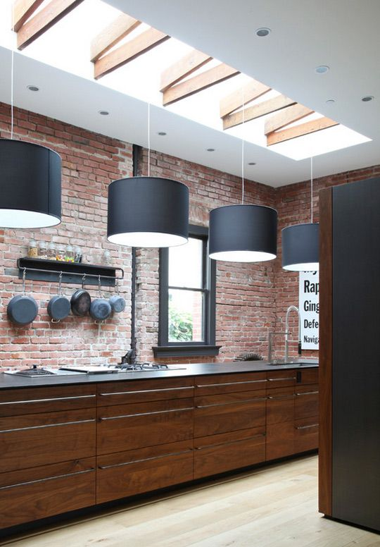 Industrial warehouse look kitchen with exposed red brick and sunlight with wooden beams. Love the hanging iron pans - adds so much character! - More industrial kitchens on http://www.stylingblog.nl