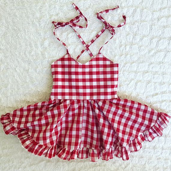 This dress is made for a picnic at the park. The fabric is a super lightweight red and white gingham print. The straps are adjustable and tie into a cross at the back. The back is elasticized for a fitted and comfortable look. The circle skirt is short and has a ruffle trim to finish off the classic look