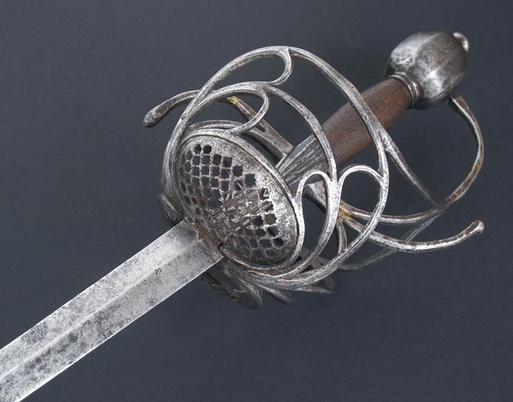 """R-289C4.- Espada de lazo """"Pappenheimer"""". Primera mitad siglo XVII. Guarnición en hierro, compuesta por una serie de gavilanes enlazados, dos principales vueltos en sentidos opuestos y guardamano, destacando las dos conchas caladas en cuadrícula. Un gran pomo facetado equilibra el conjunto. Puño en madera. Hoja recta, a dos mesas hasta la punta. Recazo punzonado."""