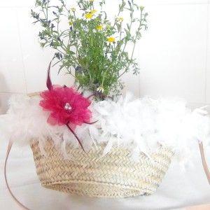 Capazo con asa de cuero claro, cruzada y cerrado con hebilla. Decorado con plumas blancas y flor fucsia.