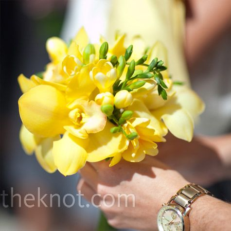 Bridesmaids hold small bunches of orchids and freesias to match the brides bouquet.