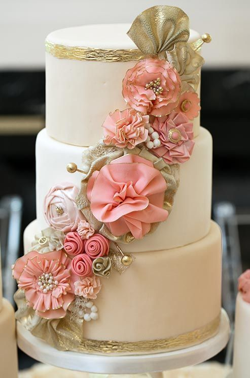 Pink and gold rosettes adorned with pearls, lace and gilded pins drape gracefully down the side of this wedding cake.