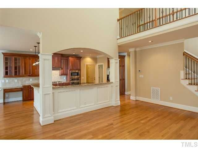Exposed Stairway And Loft Looking Into Living Room Semi Open Floor Plan With Kitchen Light Wood Floors Oak Cabinets
