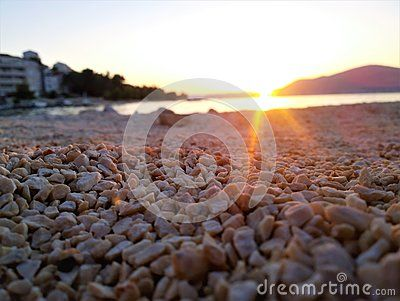 A closeup of a rocky beach with the sunset in the background.