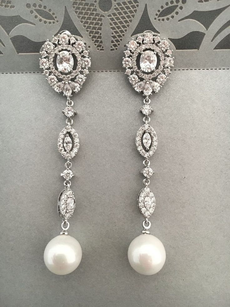 These beautiful Vintage inspired Crystal and pearl dangle bridal earrings are classic elegance!Delicate rhinestone designs with pearly white tone pearls.Setting