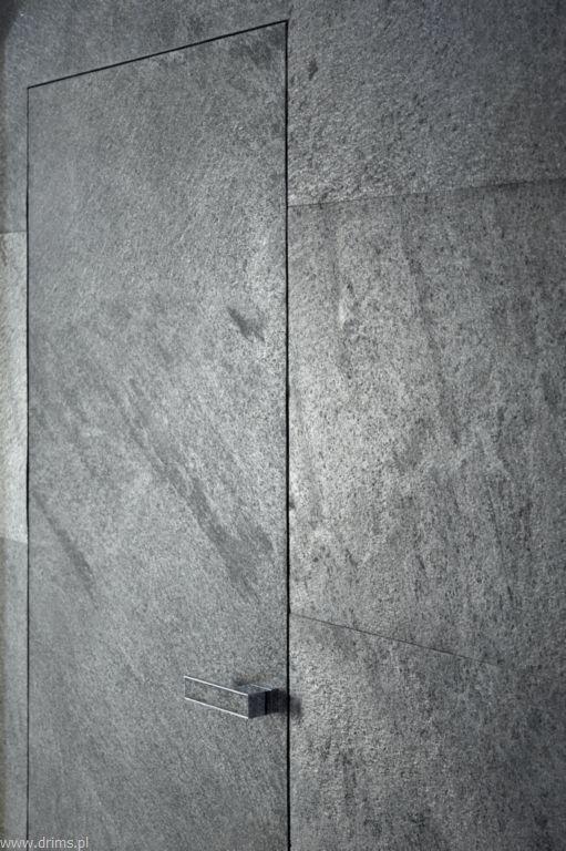DRIMS DRZWI UKRYTE     Drzwi Ukryte – drzwi niewidoczne, zlicowane ześcianą. Sąw pełni dostosowane doaranżacji wnętrza. Bez widocznych ościeżnic, zawiasów opięknym designie, anawet takiej samej powierzchni, wykończeniu ikolorystyce jak ściana. Specjalna konstrukcja skrzydła umożliwia ukrycie wszystkich elementów ościeżnicy izlicowanie jej zpowierzchnią ściany. Brak konieczności stosowania górnej belki pozwala połączyć drzwi