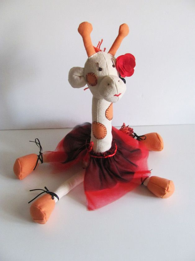 La Giraffa Ballerina ha scelto una nuova classe: Tango!  Quest'adorabile giraffa è una perfetta idea regalo per un bambino, o una decorazione originale per un appassionato di ballo.  La giraffa è realizzata con flanella e cotone, e riempita di morbida lanolina. Il tutù e le scarpette sono fatti di tulle e raso, occhi, naso e bocca sono ricamati a mano. Rosa rossa decorativa.