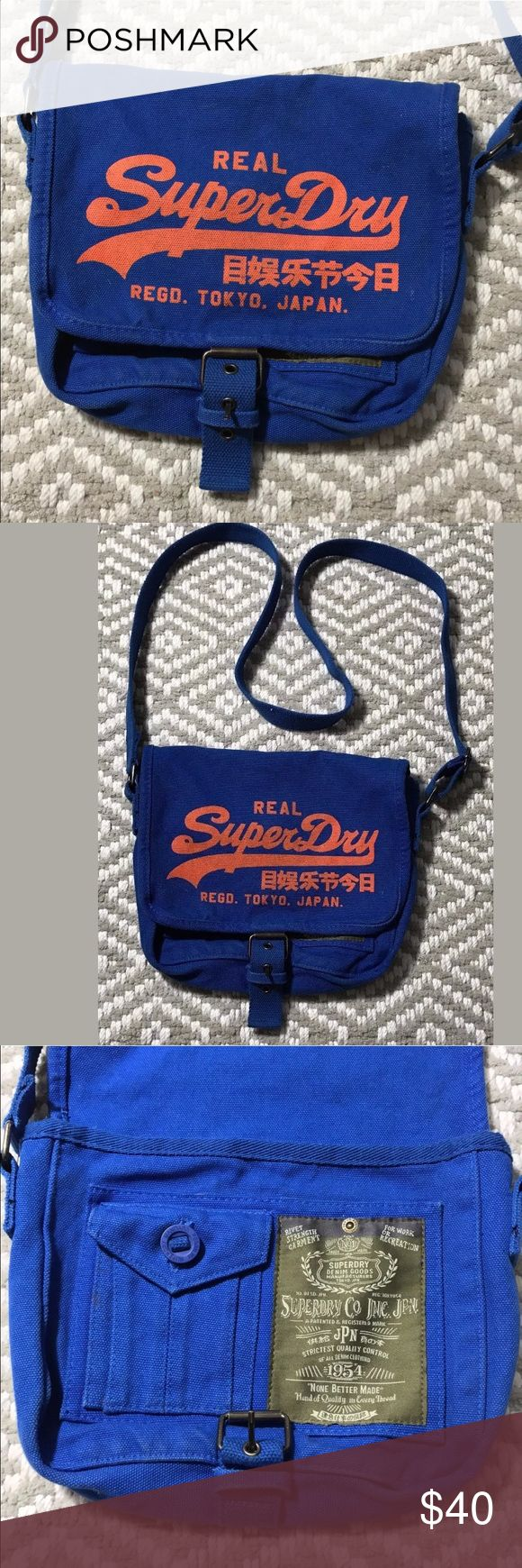 """Superdry blue crossbody messenger handbag SuperDry  Blue Canvas with orange design  Flap closes with buckle  Excellent condition  From clean, non-smoking home.  I am 100% positive and guarantee that it is authentic  10"""" x 8"""" x 2.25""""   Strap is adjustable up to a drop of 24"""" Superdry Bags Crossbody Bags"""