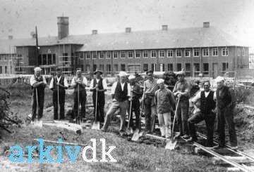 Afgravning af jord for gennemførelsen af Vesterbrogades forbindelse til Jernbanegade nr. 3 fra højre er arbejdsmand Robert Henry Sejr. I baggrunden ses stationsbygningen til Den NY Banegård under opførelse. fotograf ukendt