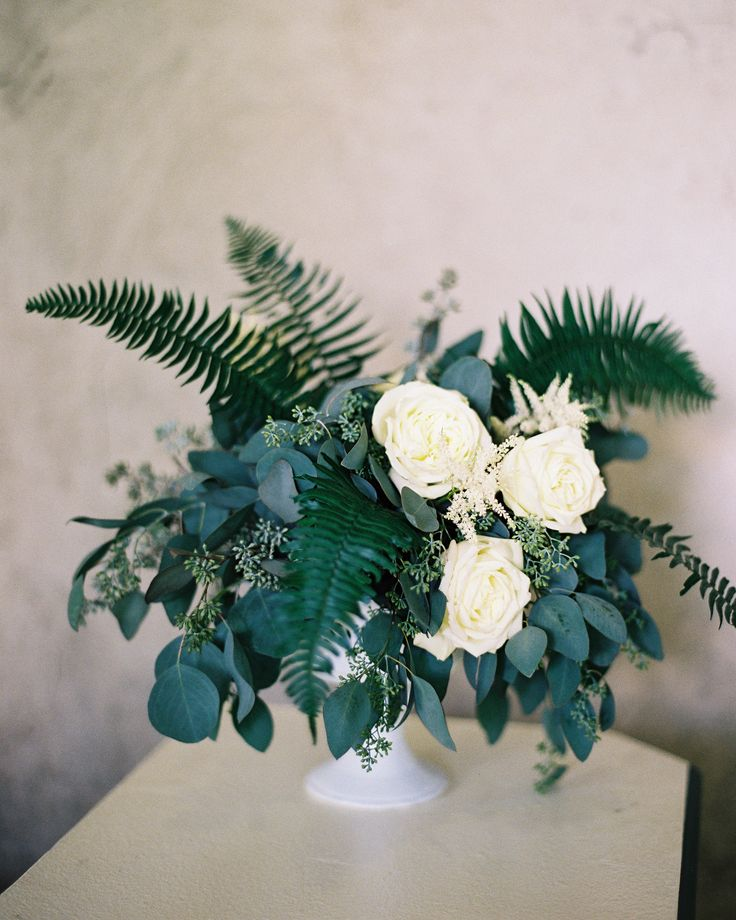 Assorted ferns and greenery paired with white roses and astilbes were fitting centerpieces for this reception held in a nature sanctuary.