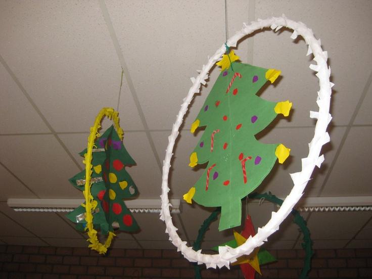Snel een plafondversiering in je klas met kerst. Een hoepel met crepepapier omwikkelen, een (ruimtelijke) ster of boom, klok o.i.d. erin hangen