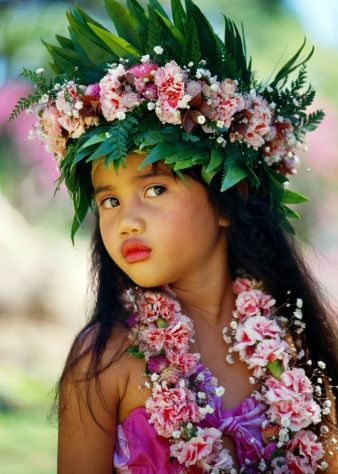 French Polynesia, Tahiti, portrait of young girl wearing head lei...