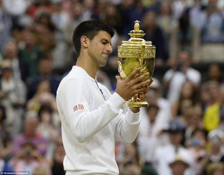 The 28-year-old holds aloft the Wimbledon trophy after successfully defending his title against Federer in a repeat of the 2014 final
