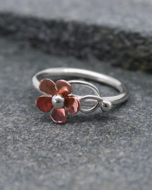 A delicate silver and copper flower ring.  The copper flower is 10mm with a silver centre and silver wire tendrils on a silver wire band.  Also available in brass with a silver bead and tendrils.  #brass #copper #daisy #flower #handmade #ring #silver #starboardjewellery #jewellery #cornwall #uk #gb #westcountry #devon #england #silversmith #pretty #jeweller #jewellers #handmadejewellery