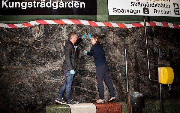"""Två av forskarna står vid väggen i tunnelbanestationen, under en skylt där det står """"Kungsträdgården""""."""