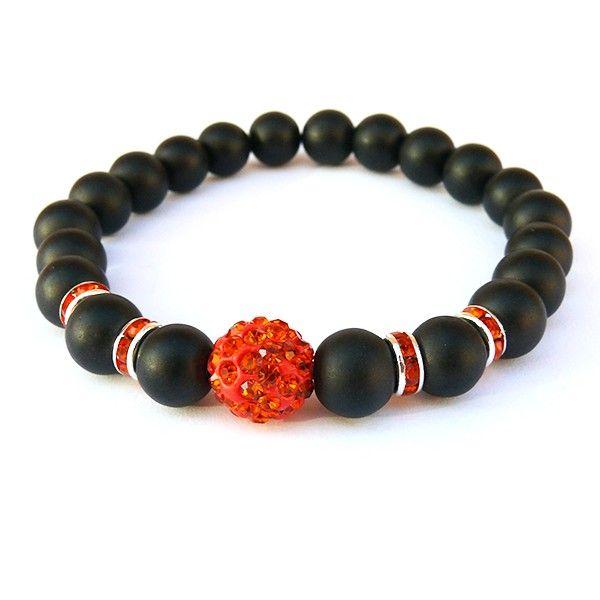 Náramek je vyrobený z černých matných skleněných korálků doplněný o rondelky s oranžovými kamínky a dominantním shamballa korálkem v barvě světle červená. Korálky jsou navlečené na lycru, která je elastická a usnadňuje navlečení i svlečení z ruky.