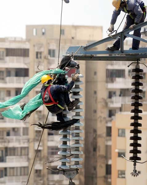 Karachi electric supply company (KESC) workers busy in their work at a high-tension electricity pylon on Tuesday, May 15, 2012.