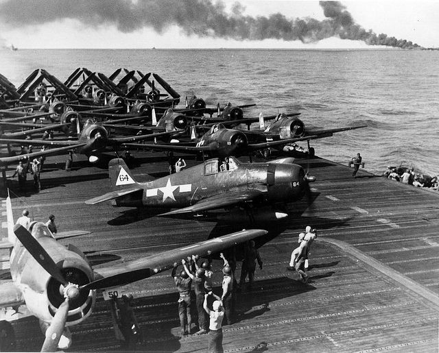 Grumman F6F's on board the aircraft carrier USS Enterprise (CV 6), 30 October 1944. In the background is the burning USS Belleau Wood hit by a kamikaze.
