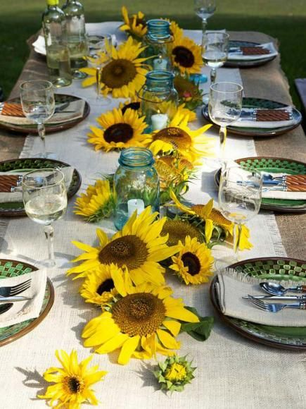 Sunny setting: Scattered sunflowers seem to grow from a burlap-covered table. Green-and-brown tableware continue the earthy theme, while sky-blue jars hold candles.