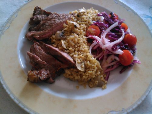 Bife vaca grelhado com bulgur, cogumelos e salada. Grilled steak with bulgur, mushrooms and salad.