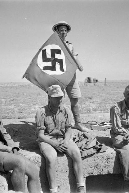A British soldier in North Africa with his captured prizes of 3 Germans and a Nazi swastika flag, June 1942.