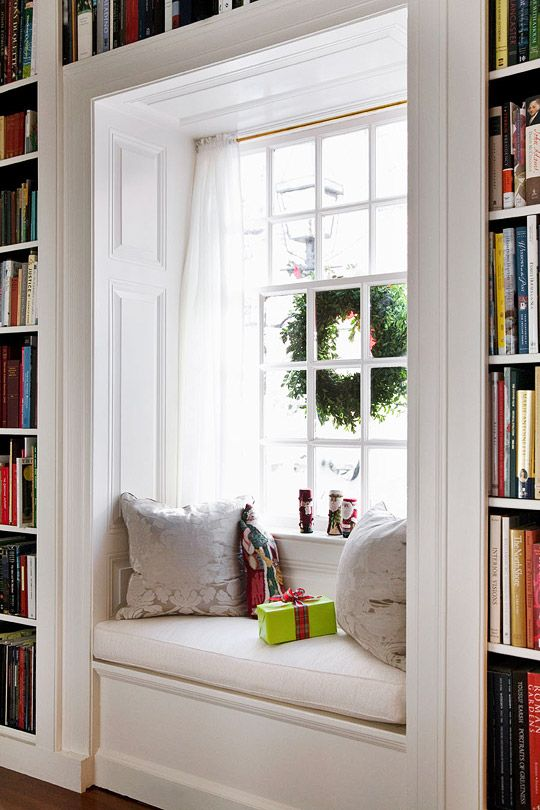 Love the woodwork in this window seat --and that it's surrounded by floor to ceiling bookshelves.