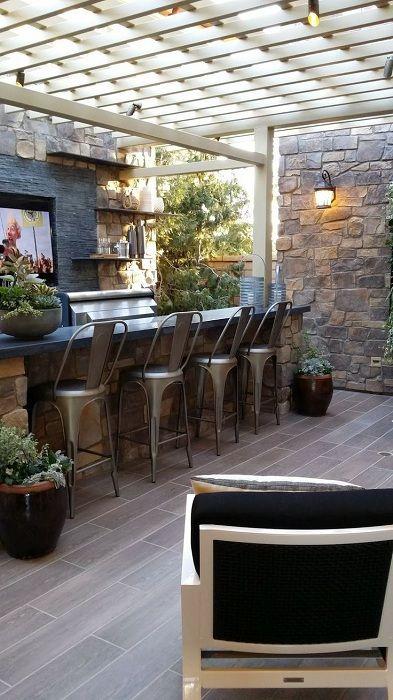 La zona del bar abierto está protegido por un gazebo blanco. taburetes de la barra en un espacio de estilo industrial hacen hincapié en la zona de recreo.