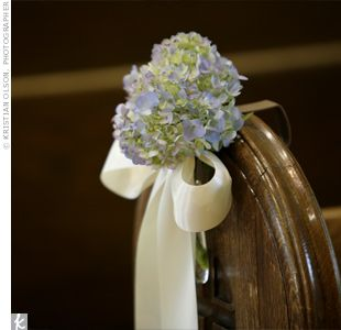 Blooms of purple hydrangeas tied with ivory ribbon adorned each pew in the chapel