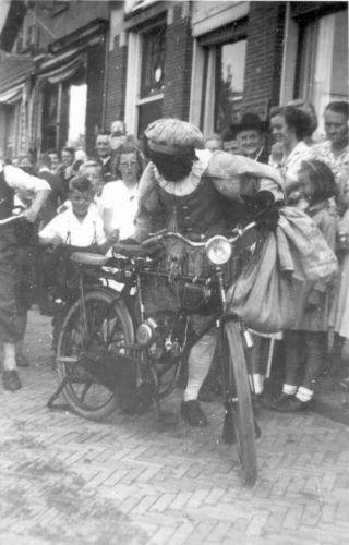 Een 'Zwarte Piet' op de motorfiets ergens in Sneek, tijdens de bevrijding. Dit soort motorfietsen werden door bijna alle rijwielfabriekanten gemaakt. Opname gemaakt kort na de Tweede Wereldoorlog.