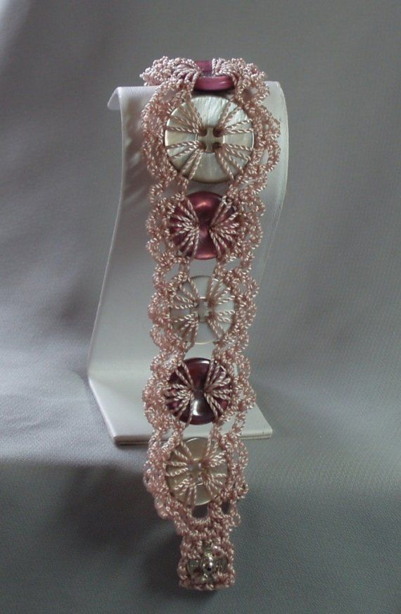 Beige thread, beige and berry colored buttons, snap closure, approximately 8 inches in length